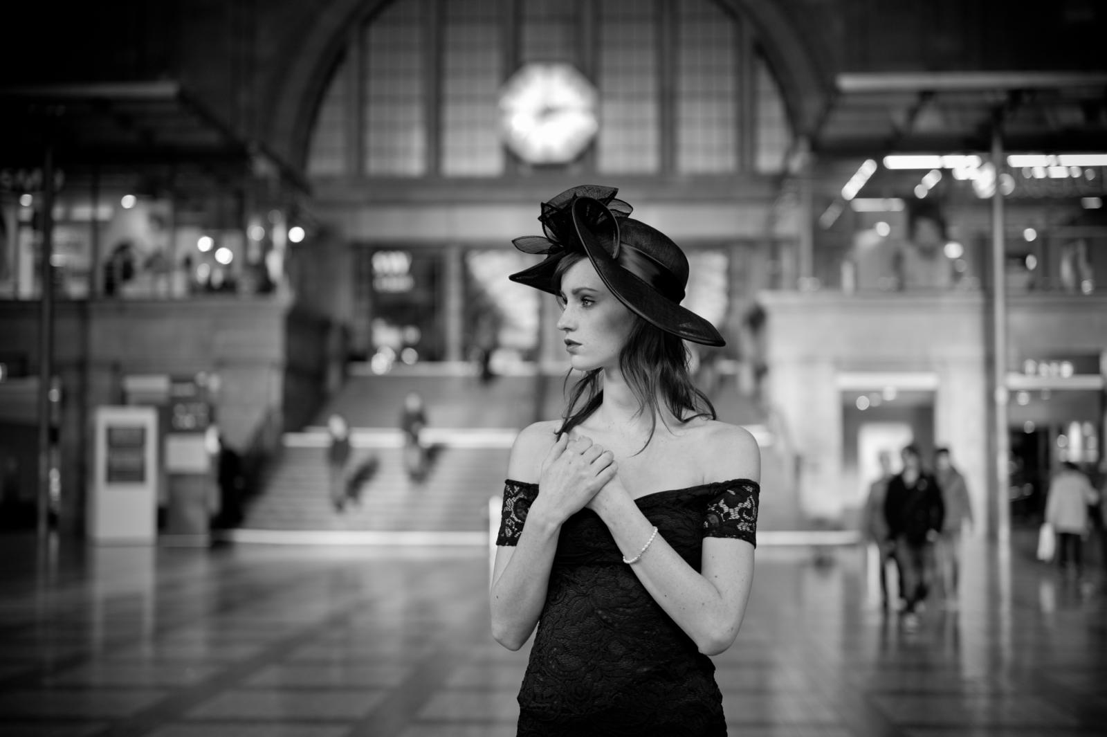 Porträt eine Frau mit Hut in einer Bahnhofshalle