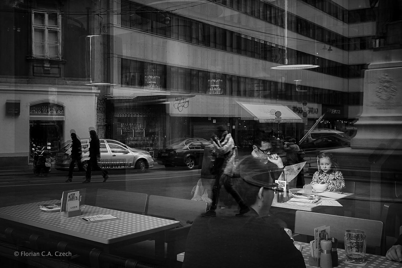 Menschen im Cafe - Straßenszene im Hintergrund