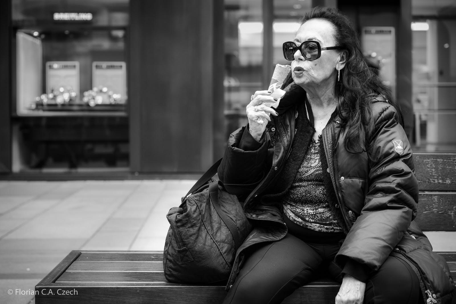Frau ist ein Eis auf einer Bank