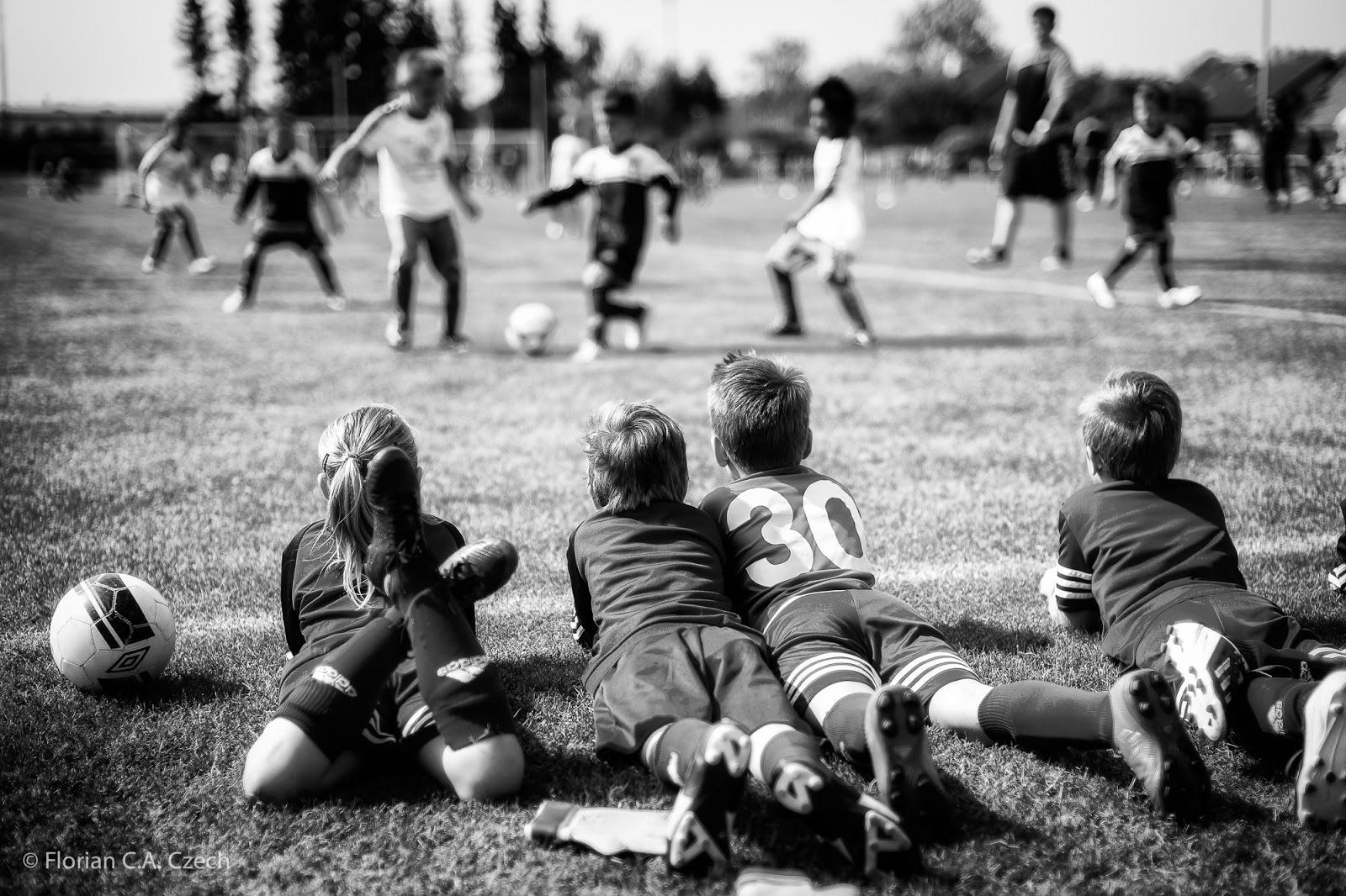 Kinder liegen auf dem Rasen und schauen beim Fussball spielen zu