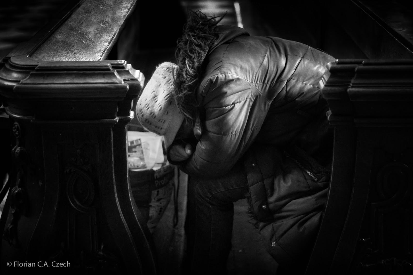 Frau wühlt in einer Mülltonne