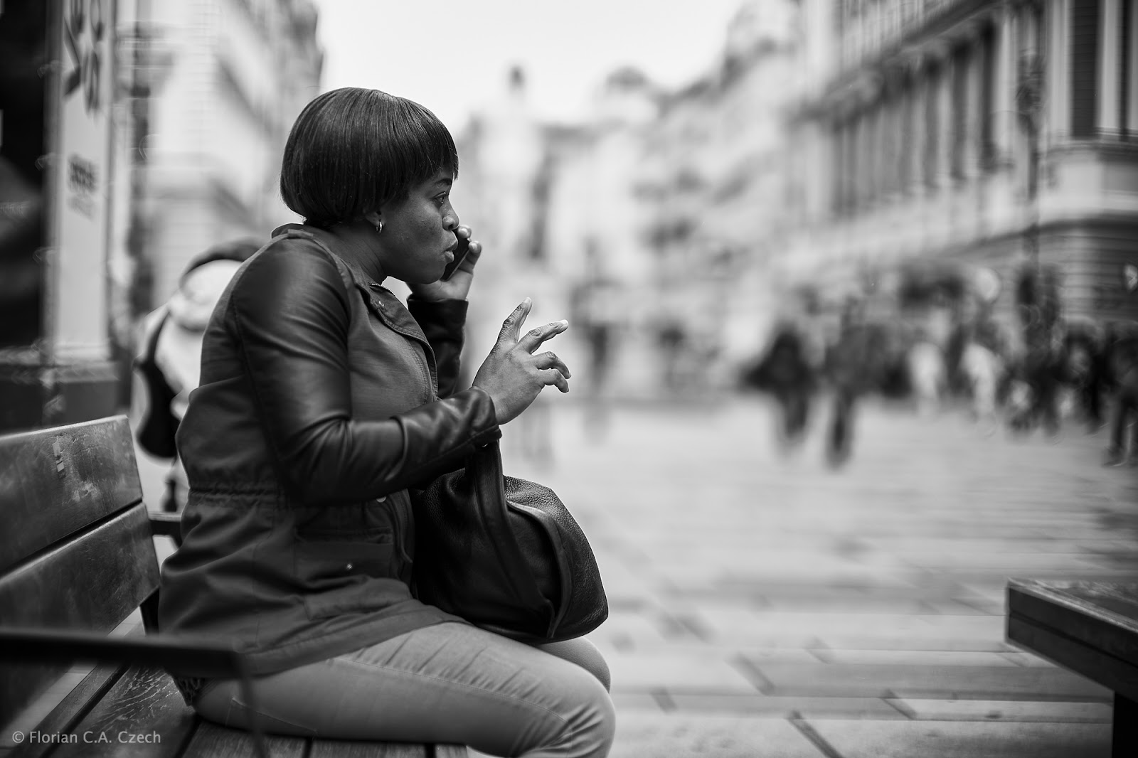 Frau sitzt auf einer Bank und telefonier
